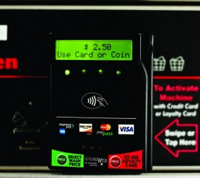An image of a SpyderWash credit card reader mounted on the front panel of a washing machine at Liberty Laundry Sheridan Store self-service coin laundromat and drop-off laundry service in Tulsa, Oklahoma.