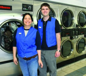 Two smiling happy laundry attendants named Maricruz and Brian wearing blue vests with name tags standing in front of a row of high capacity dryers at Liberty Laundry Sheridan Store self-service coin laundromat and drop-off laundry service in Tulsa, Oklahoma.