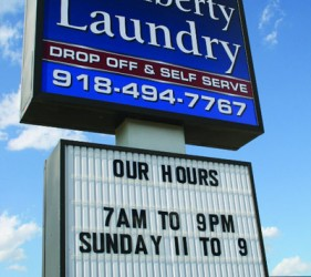 "An image of the street sign for Liberty Laundry Sheridan Store self-service coin laundromat and drop-off laundry service in Tulsa, Oklahoma. The sign says, ""Our [Store] Hours: 7 A.M. to 9 P.M., Sunday 11 A.M. to 9 P.M."""