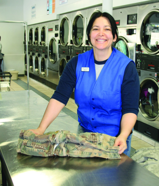 A happy laundry attendant folding clothes and smiling at the camera at Liberty Laundry.