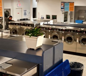 An interior image of Liberty Laundry Sheridan Store self-service coin laundromat and drop-off laundry service in Tulsa, Oklahoma. The image shows rows of stainless steel Speed Queen high capacity washers and dryers.