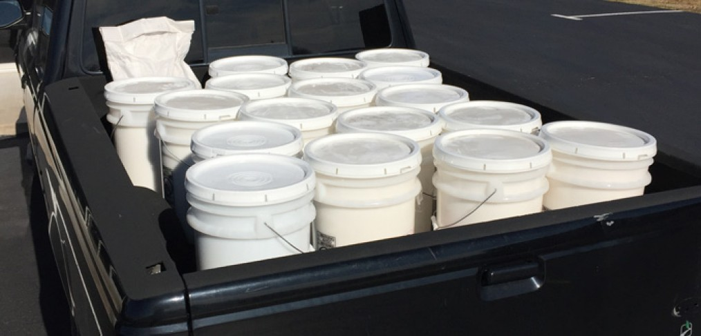 A pickup with several buckets of powdered soap sitting in the bed of the truck in the parking lot outside Liberty Laundry.