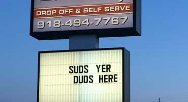"A street sign at Liberty Laundry that says, ""Suds your duds here."""